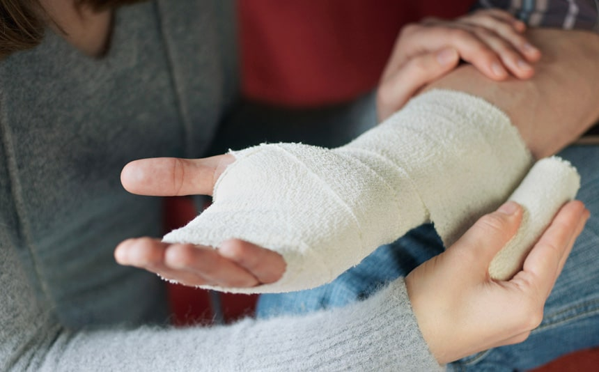 Woman bandages man's hand